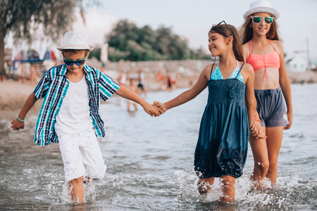 Happy children running together through the water  and holding hands at the beach. Summer vacation and healthy lifestyle concept 写真素材