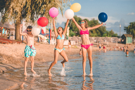 Happy kids jump and having fun with balloons in the water, on the beach. - Image