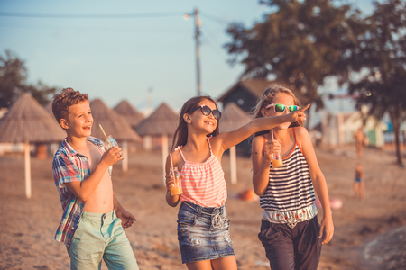 Portrait of happy children while having fun walking on the beach at the day time. - Image