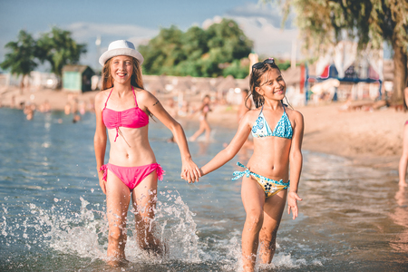 Happy little girls running through the water at the beach - Image 写真素材