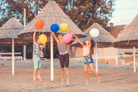 Happy children having fun with color balloons while jumping on the sandy beach. - Image 写真素材