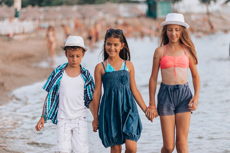 Happy children walking together through the water  and holding hands at the beach - Image 写真素材