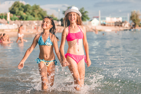 Happy two little girls running together through the water and holding hands at the beach - Image