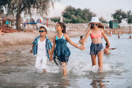 Happy children running together through the water  and holding hands at the beach - Image
