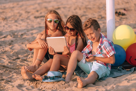 Portrait of positive children playing with digital tablet together on sandy beach.