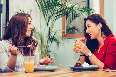 Two beautiful young women enjoying cake and juice together in a cafe sitting at a table laughing and gossiping with happy smiles - Image