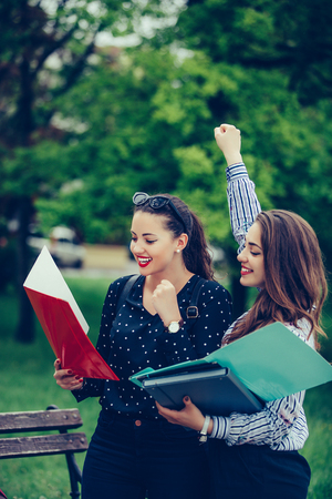 Two female friends, students celebrating success for approved exams in a park