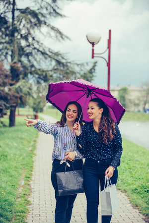 Two female best friend walking by the river with umbrella above head.They smiling and making fun. Raining day. - Image