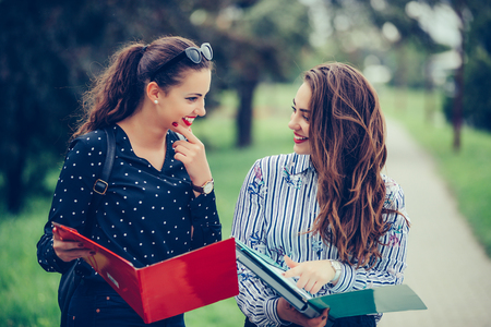 Two beautiful female friends, students checking paper notes before exam