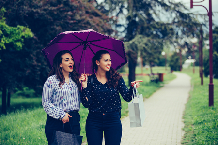 Two female best friend walking through the park with umbrella above head.They smiling and pointing away in the street. Raining day.
