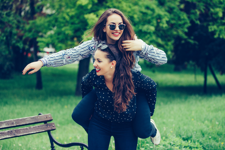 Outdoor shot of young woman carrying her female friend on her back. Two young woman having fun in the park.