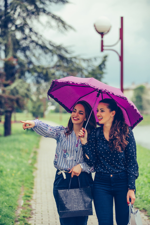 Two female best friend walking by the river with umbrella above head.They are smiling and making fun. Raining day.