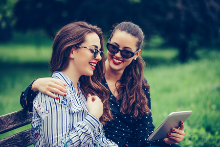 Two beautiful girls are using a digital tablet, talking, hugging and smiling while sitting on the bench outdoor.