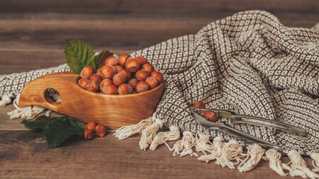 Hazelnuts with green leaves in wooden bowl on rustic brown background.