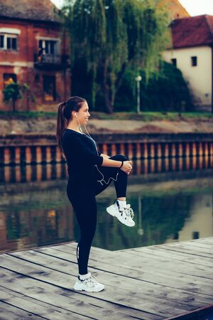 Young beautiful woman listening to music and doing stretching exercises by the river
