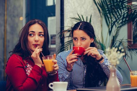 Image of a two happy girls friends sitting in cafe talking with each other drinking coffee,  looking at someone.