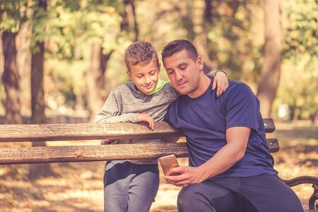 Little boy and his father taking a break after workout and watching something on smart phone in the park. Father and son spend time together and lead a healthy lifestyle.