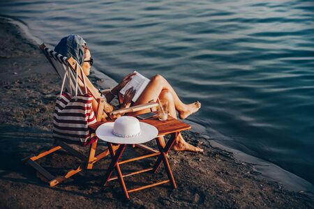 Beautiful young woman in a swimsuit with a towel on her head sitting on deck chair on the beach enjoying while reading a book