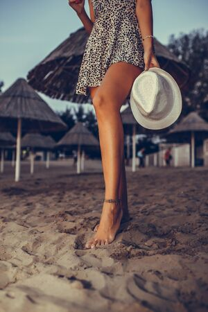 Young pretty girl in a dress walking on sandy beach in the evening while holding hat in her hand. Woman legs Zdjęcie Seryjne