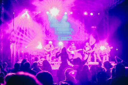 Folla di concerti che assiste a un concerto, le sagome di persone sono visibili, retroilluminate da luci di scena. Mani alzate e smartphone sono visibili qua e là.