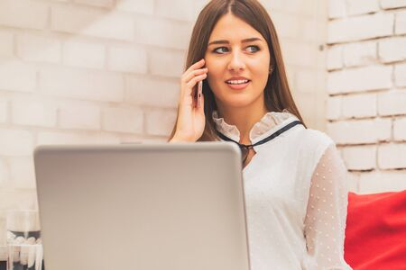 Attractive young woman working on a laptop computer and talking on her cellphone in a coffee shop Stockfoto