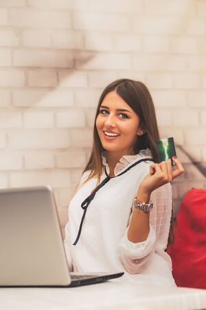 Young woman holding credit card and using laptop computer. Online shopping concept Stockfoto