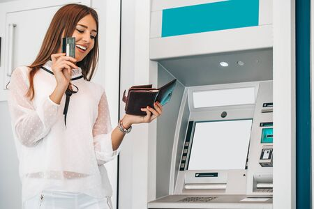 Attractive young woman withdrawing money from credit card at ATM