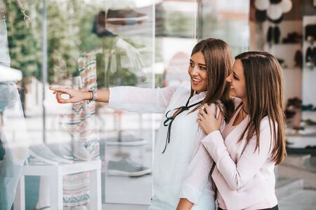 Two young beautiful women enjoy shopping while pointing finger in the shop window