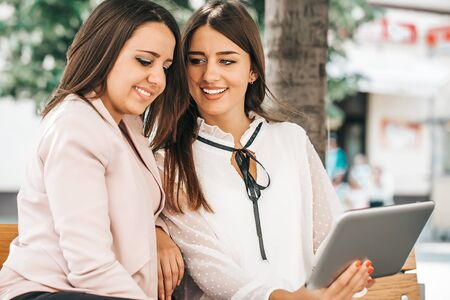 Two beautiful women laughing watching media content together in a digital tablet, sitting on a bench in the city. Stockfoto