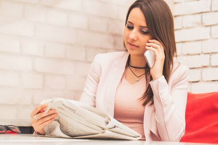 Young unemployed female doing job hunting and reading employment announcements.The woman is sitting in cafe holding a newspaper and does a phone call to arrange an interview. Stockfoto