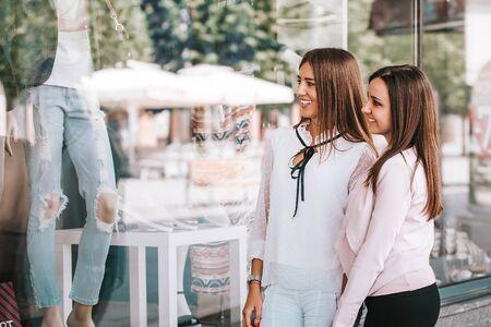 Two young beautiful women enjoy shopping while looking shop windows together.