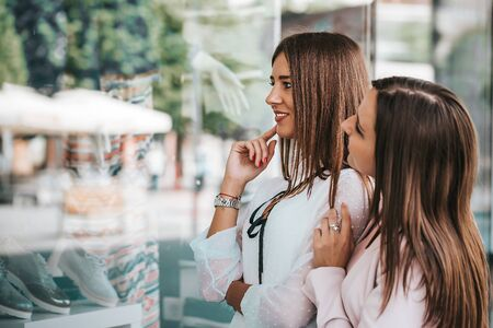 Close up portrait of two young beautiful women enjoy shopping while looking shop windows together.