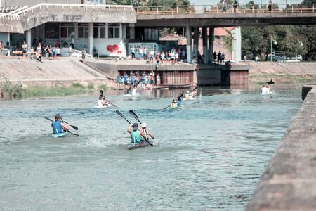 Team of a young man and woman athlete on rowing kayak on lake during competition. Followers watch a Kayak local competition.