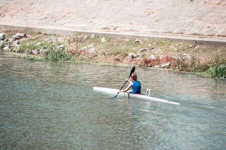 Young woman athlete on rowing kayak on lake during competition
