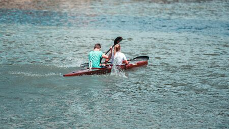 Team of a young man and woman athlete on rowing kayak on lake during competition Stockfoto