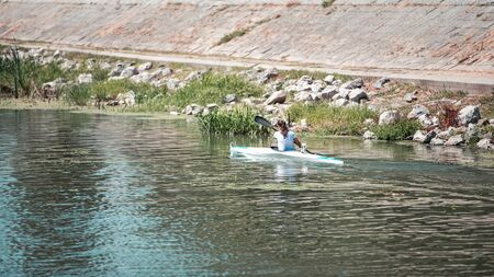 Young woman kayaking on the lake, she is competing in rowing