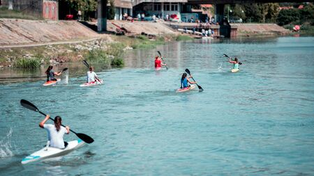 Young women athletes on rowing kayak on lake during competition