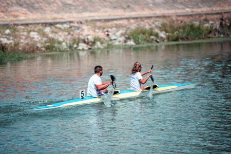 Team of a young man and woman athlete on rowing kayak on lake during competition. Focus on water