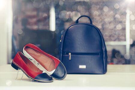 Pair of stylish women leather shoes with backpack in the background in a store. Stockfoto