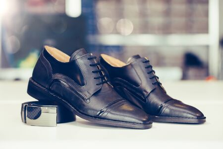 Pair of  black elegant leather shoes and belt on a shelf of a shop. Copy space.