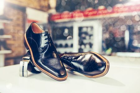 Pair of elegant leather shoes and belt on a shelf of a shop. Copy space.