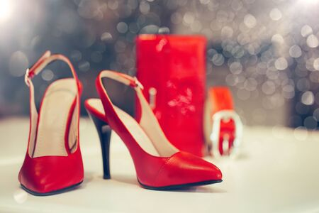 Close up shot of red elegant high heel women shoes or sandals , with woman wallet and belt  in the background. Stockfoto