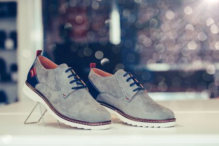Pair of gray casual leather shoes on a shelf of a shop. Copy space. Stockfoto