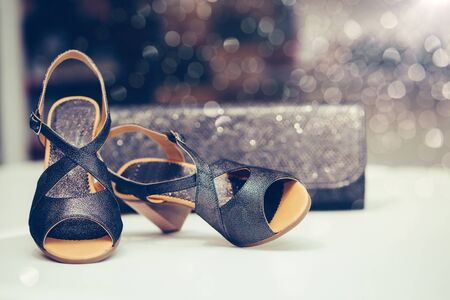 Close up shot of black elegant high heel women shoes or sandals , with woman purse.