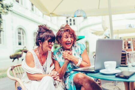 Two excited senior women reading good news on line with a laptop  in outdoor cafe