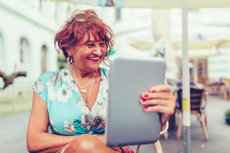 Senior woman reading a message, e-book or information on her tablet computer with a look of excited anticipation as she sitting in outdoor cafe.