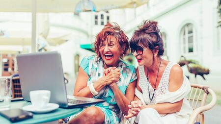 Two excited senior women reading good news online on laptop while sitting in a outdoor cafe. Stockfoto