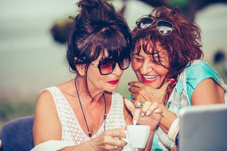 Close up portrait of two happy senior women laughing and having fun while drinking coffee in a outdoor cafe. Stockfoto