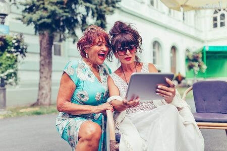 Two senior women sitting in outdoor cafe laughing and watching social media and funny viral videos on a tablet.