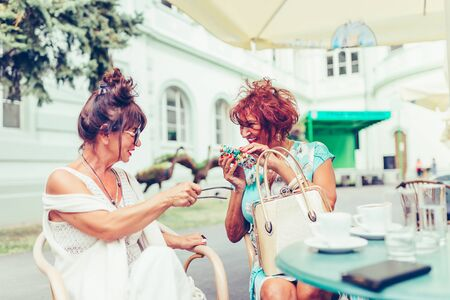 Two happy senior women talking and drinking coffee sitting in the table in a outdoor cafe. Senior woman showing her friend her new eye glasses.